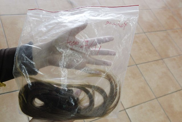 Pamela Matus holds a bag of her hair that was cut by stylist Marcelo Avatte which she is donating to make a natural hair wig for a girl undergoing chemotherapy for cancer, in Vina del Mar, August 8, 2014. (Photo by Rodrigo Garrido/Reuters)