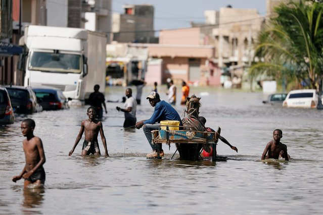 Residents walk through a flooded street after last week's heavy rains in Keur Massar, Senegal on September 8, 2020. (Photo by Zohra Bensemra/Reuters)