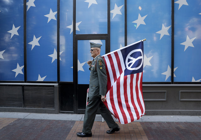 A protester carrying a peace flag walks in downtown Cleveland, Sunday, July 17, 2016, in preparation for the Republican National Convention that starts Monday. (Photo by Patrick Semansky/AP Photo)
