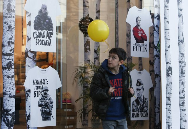 A teenager holding a balloon from McDonald's stands outside a shop selling T-shirts printed with images of Russia's President Vladimir Putin, near an outlet of the fast food restaurant in central Moscow November 19, 2014. The McDonald's restaurant, which was the first one to open in Russia and then temporarily closed by the state food safety watchdog this August, was reopened on Wednesday, according to local media. (Photo by Sergei Karpukhin/Reuters)