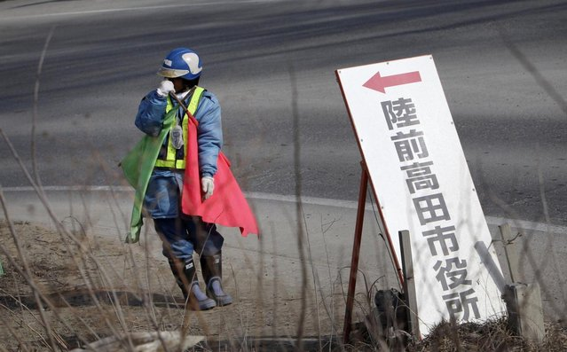 "In this Friday, February 22, 2013 photo, standing by a signboard reading: ""Rikuzentakata City Hall"" a worker holds flags to control traffic under cold weather in a street near a new road construction site in Rikuzentakata, Iwate Prefecture. Japan's progress in rebuilding from the tsunami that thundered over coastal sea walls, sweeping entire communities away, is mainly measured in barren foundations and empty spaces. (Photo by Junji Kurokawa/AP Photo)"