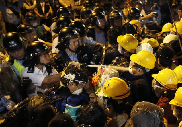 A policeman uses pepper spray while clashing with pro-democracy protesters during a rally close to the chief executive office in Hong Kong, November 30, 2014. (Photo by Tyrone Siu/Reuters)
