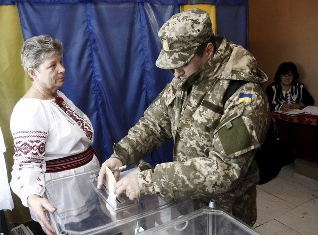 A Ukrainian serviceman casts his ballot during a regional election at a polling station near Lviv, Ukraine, October 25, 2015. Ukrainians go to the polls on Sunday to appoint mayors and council heads to regional seats. (Photo by Roman Baluk/Reuters)