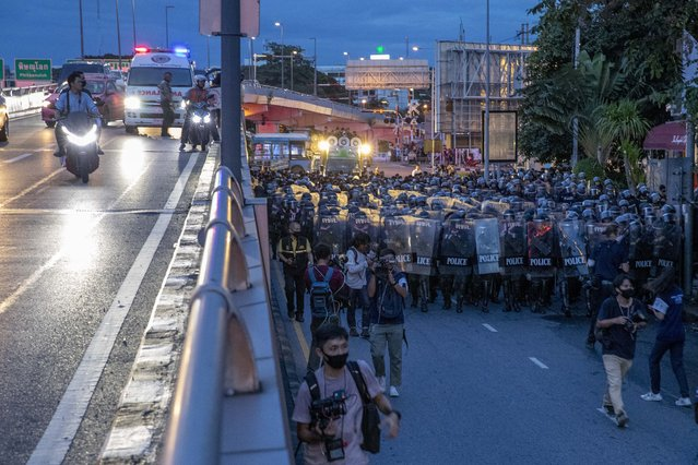 Riots police officers march chasing a small group of pro-democracy protesters close to Government House in Bangkok, Thailand, Thursday, October 15, 2020. Riot Police disperse encampment of pro-democracy demonstrators who had camped out overnight after they had marched to Government House – the venue of the prime minister's office on Wednesday, Oct. 14. (Photo by Gemunu Amarasinghe/AP Photo)