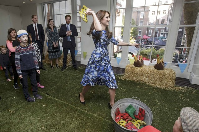 Britain's Kate, Duchess of Cambridge takes part in welly wanging, as Prince William (L) and Prince Harry watch, with children and representatives from charities and Aardman Animations, during a meeting of the Charities Forum at the British Academy of Film and Television Arts (BAFTA) in London, October 26, 2015. (Photo by Tim Ireland/Reuters)