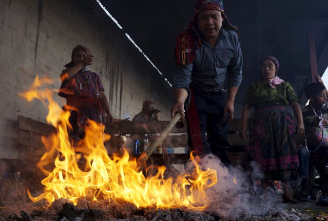A mayan priest prepares a fire outside of San Simon church in Iztapa, in Chimaltenango, around 62 km (39 miles) from Guatemala City, October 28, 2015. (Photo by Jorge Dan Lopez/Reuters)