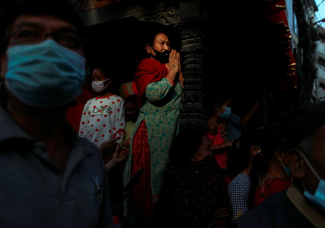A devotee wearing a protective face mask prays during a chariot procession of Pachali Bhairab amid the spread of coronavirus disease (COVID-19), in Kathmandu, Nepal on October 21, 2020. (Photo by Navesh Chitrakar/Reuters)