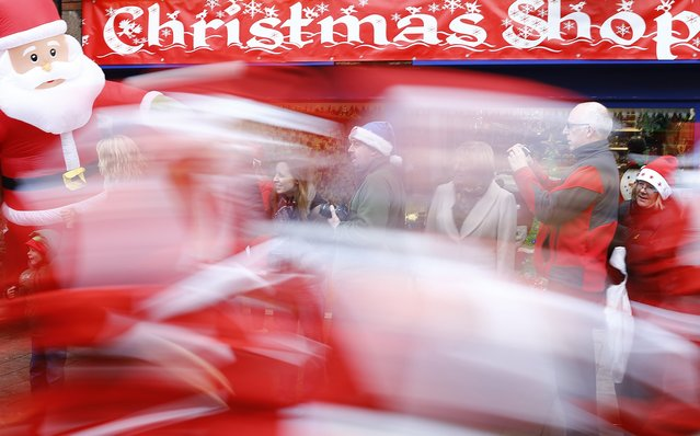 Competitors dressed as Santa Claus sprint past spectators during an annual charity Santa fun run in Loughborough, central England December 7, 2014. (Photo by Darren Staples/Reuters)