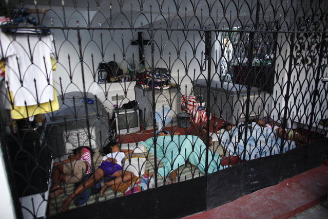 A family sleeps in a mausoleum, which serves as their home, inside the Manila North Cemetery, October 28, 2011. (Photo by John Javellana/Reuters)