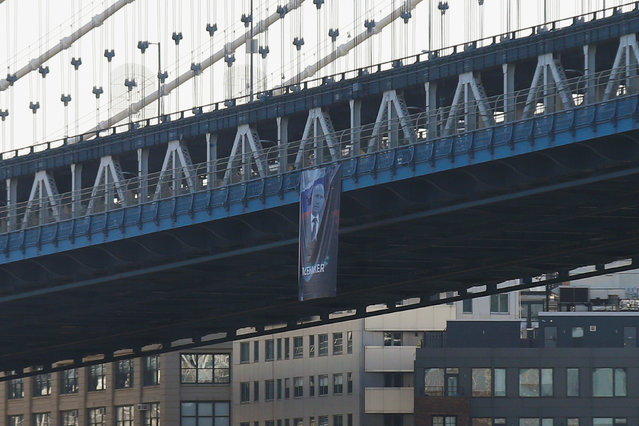 A banner with an image of Russian President Vladimir Putin hangs from the Manhattan Bridge in New York City, U.S., October 6, 2016. (Photo by Brendan McDermid/Reuters)