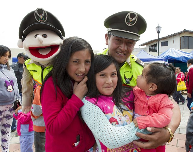 A police officer poses for a photograph with children and youths after performing with a puppet for an educational campaign on children's rights, in Tulcan November 2, 2015. (Photo by Guillermo Granja/Reuters)