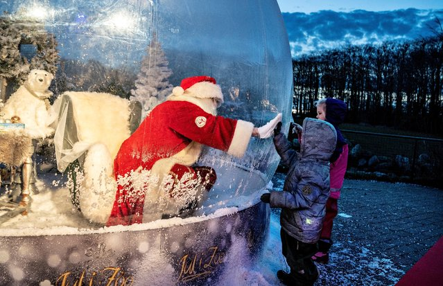 A Santa is seen in a coronavirus-safe plastic bubble at the Zoo in Aalborg on November 13, 2020. (Photo by Henning Bagger/Ritzau Scanpix/AFP Photo)
