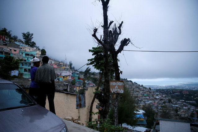 """A couple enjoy the view while Hurricane Matthew approaches Port-au-Prince, Haiti, October 3, 2016. The text reads, """"House for sale"""". (Photo by Carlos Garcia Rawlins/Reuters)"""