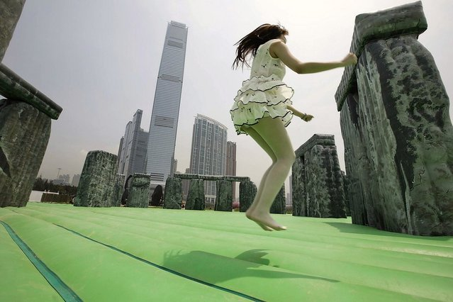 "A member of the public bounces on a life-size interactive inflatable sculpture of Stonehenge called ""Sacrilege 2012"" by English contemporary artist Jeremy Deller on display as part of the ""Inflation!"" exhibition curated by Mobile M + on April 24, 2013 in Hong Kong. The inflatable artwork is one of six on display as part of the exhibition which is open from April 25, 2013 until June 9, 2013. (Photo by Jessica Hromas)"