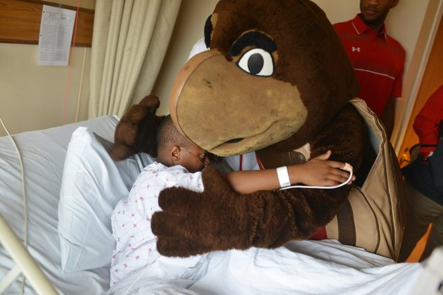 From left to right, Aaron Davis, 9 is embraced by  the  University of Maryland Terrapin at MedStar Harbor Hospital in Baltimore, Maryland on November 10, 2015 