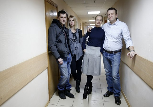 Russian opposition activist and anti-corruption crusader Alexei Navalny, 38, right, his wife Yulia, second right, and his brother Oleg Navalny, left, with his wife, pose for journalists  at a court in Moscow, Russia, Tuesday, December 30, 2014. The Moscow court on Monday moved up the date of its verdict in a criminal case against President Vladimir Putin's top foe Navalny in an apparent bid to derail a planned protest. (Photo by Pavel Golovkin/AP Photo)