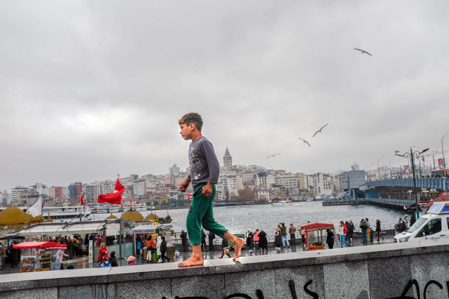 A child walks barefoot at Eminonu Square in Istanbul on December 15, 2020. Turkey has announced a four-day lockdown starting New Year's Eve until the morning of January 4, 2021, in an attempt to curb the spread of COVID-19. The government this month re-introduced weekend lockdowns as well as nighttime curfews amid a spike in infections and deaths. It has avoided a full lockdown since the beginning of the pandemic to keep the economy running. (Photo by Bulent Kilic/AFP Photo)
