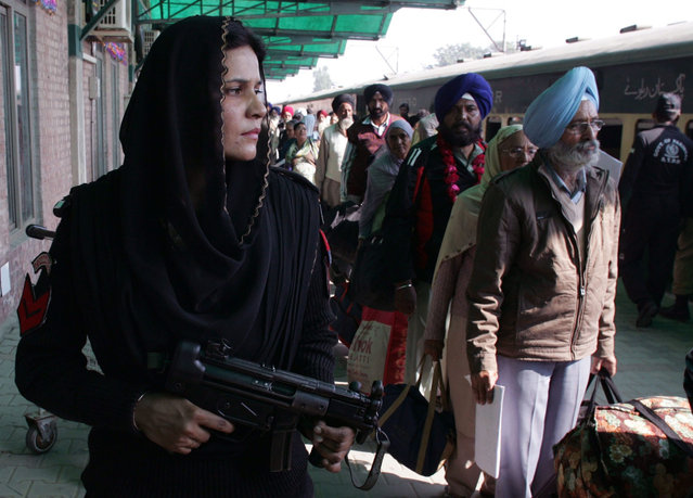 A Pakistani female police commando stands guard, as Indian Sikh pilgrims arrive at Wagah railway station near Lahore, Pakistan, Friday, November 20, 2015. Hundreds of Indian Sikh pilgrims arrived in Pakistan by a special train to participate in three-day festival to celebrate the 547st birth anniversary of their spiritual leader Baba Guru Nanak, the founder of Sikh religion, at Nankana Sahib near Lahore. (Photo by K.M. Chaudary/AP Photo)