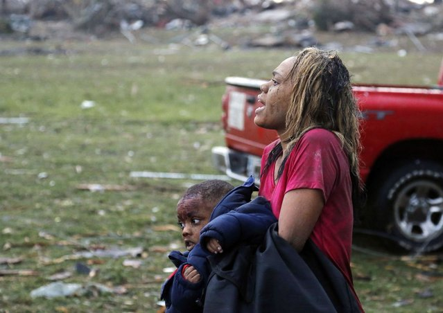 A woman carries an injured child to a triage center near the Plaza Towers Elementary School in Moore, Okla., Monday, May 20, 2013. A tornado as much as a mile (1.6 kilometers) wide with winds up to 200 mph (320 kph) roared through the Oklahoma City suburbs Monday, flattening entire neighborhoods, setting buildings on fire and landing a direct blow on an elementary school. (Photo by Sue Ogrocki/AP Photo)