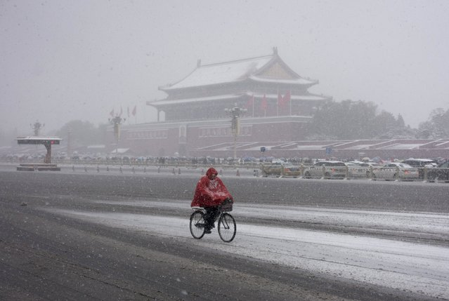 A resident rides a bicycle along the Chang'an Avenue past the Tiananmen Gate amid heavy snowfall in Beijing, China, November 22, 2015. (Photo by Reuters/Stringer)