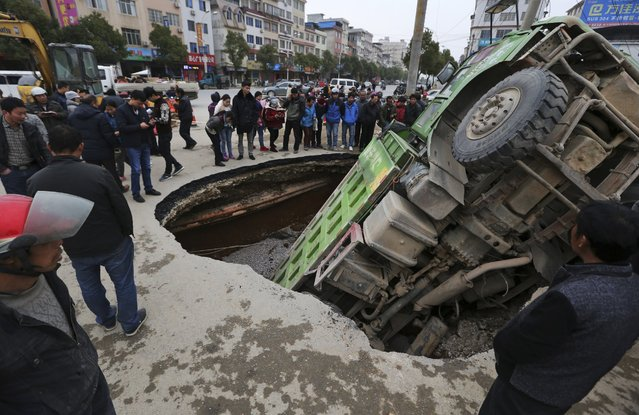 People look at a loaded truck that got stuck in a sinkhole on a road in Guilin, Guangxi Zhuang Autonomous Region, January 7, 2015. No injury was reported, according to local media. (Photo by Reuters/Stringer)