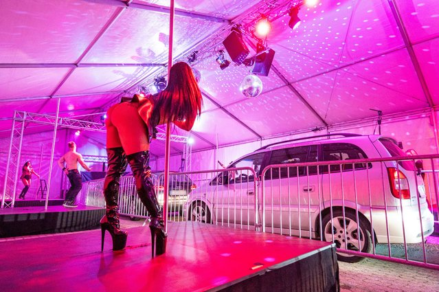 Dancers stand in strip-drive-in on stages in front of cars in Landshut, Bavaria on May 29, 2020. In the Strip-Drive-In the car passengers can admire the strippers at the prescribed minimum distance. The shows take place on Friday and Saturday between 11pm and 3am local time and cost €35. Motorists are allowed into the tent but only for around 15 minutes. (Photo by Armin Weigel/dpa)