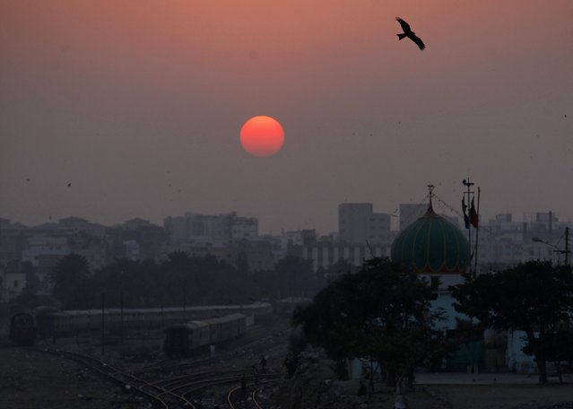 A bird flies over a shrine as the sun sets in Karachi December 31, 2014. (Photo by Akhtar Soomro/Reuters)