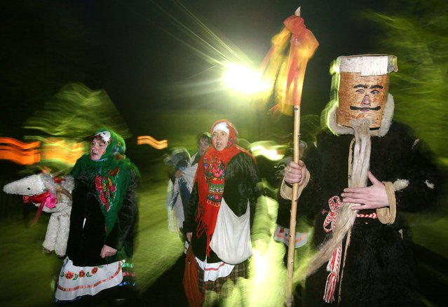 Belarussians in costumes sing songs during the traditional rite of Shchadrets (Schedry vecher or Generous Eve) in the village of Osovo, some 190 km from Minsk, Belarus, 13 January 2015. Shchadrets is a Belarusian folk holiday celebrated on the New Year's Eve in accordance with the Julian calendar (Old New Year). (Photo by Tatyana Zenkovich/EPA)