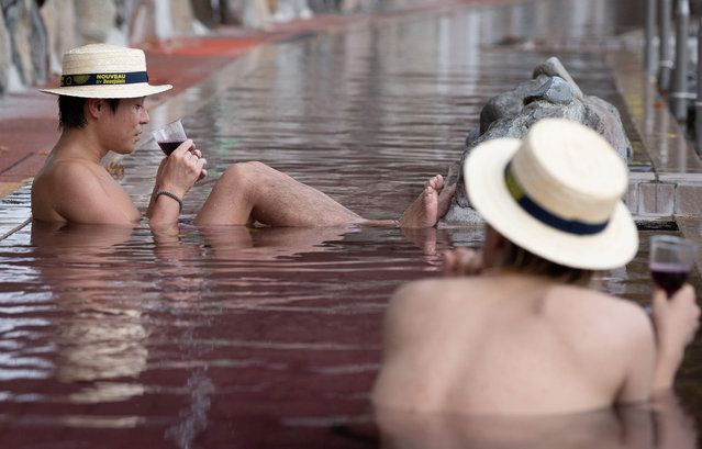 """People enjoy 2020 Beaujolais Nouveau wine as they bathe in a """"wine bath"""", colored hot water, on the day of the Beaujolais Nouveau official release, at Hakone Kowakien Yunessun hot spring resort in Hakone, Japan, 19 November 2020. Japan is a major market for the Beaujolais Nouveau. (Photo by Pierre Emmanuel Deletree/SIPA Press)"""