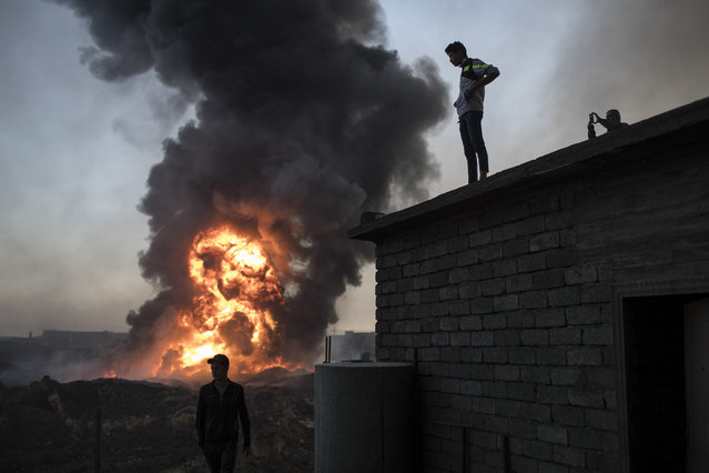 People watch as safety workers try to extinguish fire from a burning oil field in Qayara, south of Mosul, Iraq, Thursday, November 3, 2016. (Photo by Felipe Dana/AP Photo)