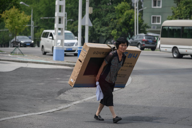 A woman carries a boxed flat-screen television on her back as she crosses a road in Pyongyang on June 17, 2018. Donald Trump dangled the carrot of foreign investment in front of North Korean leader Kim Jong Un at their nuclear summit, but analysts say few will want to put money into one of the highest-risk business environments in the world. (Photo by Ed Jones/AFP Photo)