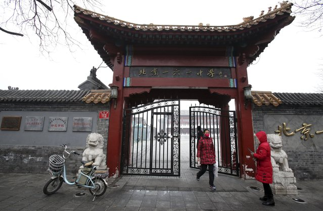 "A student (C) walks out of the entrance of a high school, which is closed after the city issued its first ever ""red alert"" for air pollution, amid heavy smog in Beijing, China, December 8, 2015. (Photo by Reuters/China Daily)"