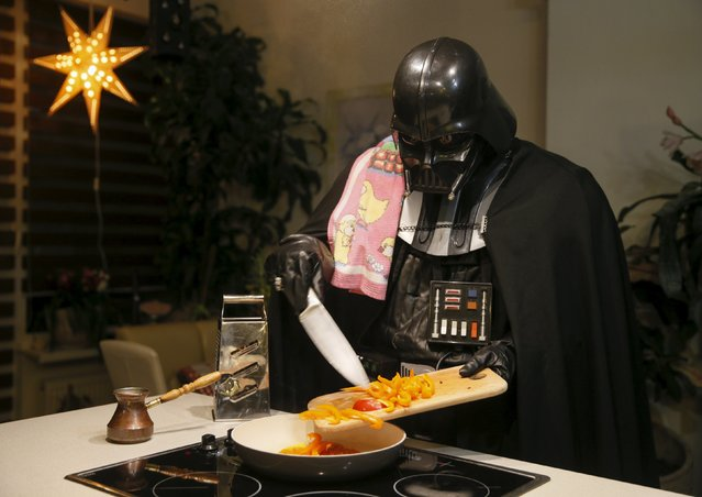 Darth Mykolaiovych Vader, who is dressed as the 'Star Wars' character Darth Vader, poses for a picture as he cooks in the kitchen of his apartments in Odessa, Ukraine, December 2, 2015. (Photo by Valentyn Ogirenko/Reuters)