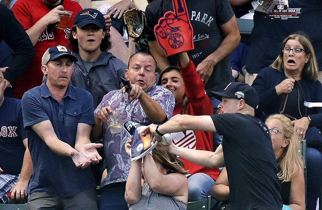 A fan covers her face with a Boston Red Sox publication as others try to catch a home run hit by Red Sox's Eduardo Nunez during the second inning of the team's baseball game against the Los Angeles Angels at Fenway Park in Boston, Wednesday, June 27, 2018. (Photo by Charles Krupa/AP Photo)