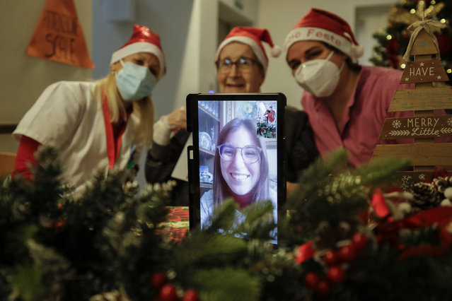 """Carolina Previtali, 93, center, is flanked by director Maria Giulia Madaschi, left, and carer Melania Cavalieri as she talks on a video call with Eleonora Nola, a donor unrelated to her, who bought and sent her a Christmas present through an organization dubbed """"Santa's Grandchildren"""", at the Martino Zanchi nursing home in Alzano Lombardo, one of the area that most suffered the first wave of COVID-19, in northern Italy, Saturday, December 19, 2020. (Photo by Luca Bruno/AP Photo)"""