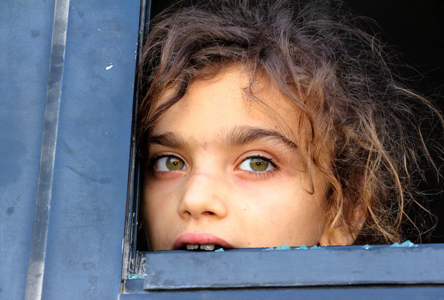 An evacuated Syrian girl from the area of Fuaa and Kafraya in the Idlib province, looks out of a broken bus window as it passes the al- Eis crossing south of Aleppo during the evacuation of several thousand residents from the two pro- regime towns in northern Syria on July 19, 2018. As the buses passed through rebel- held territory, people threw rocks at them, which shattered the windows during the evacuation which put an end to one of the longest sieges of the country' s seven- year civil war. Fuaa and Kafraya were the last remaining areas under blockade in Syria and a rare example of pro- government towns surrounded by rebel forces. (Photo by Ibrahim Yasouf/AFP Photo)
