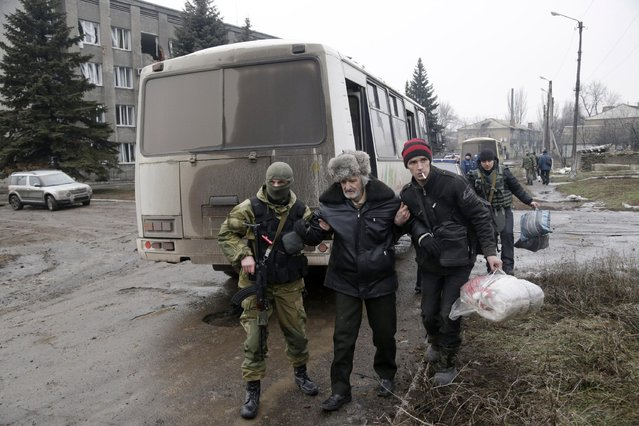 An elderly man is helped to board a bus to leave the town of Debaltseve in Artemivsk, Ukraine, Tuesday, February 3, 2015. (Photo by Petr David Josek/AP Photo)