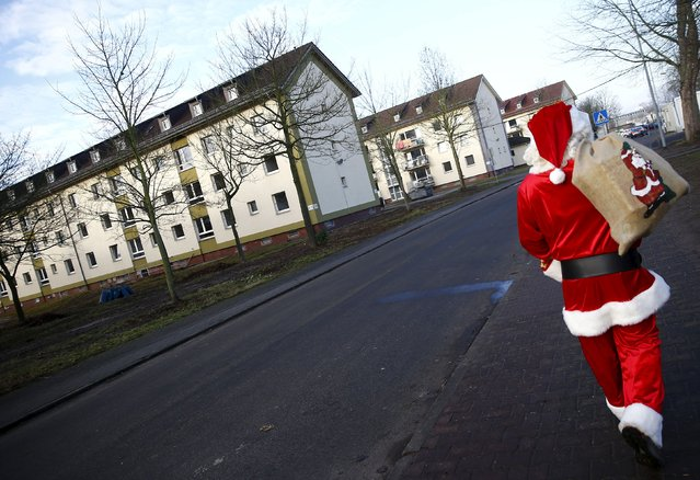 """A volunteer dressed as Father Christmas arrives for a Christmas gathering organized by local relief organization """"Die Johanniter"""" with presents for the children at the former US army barracks used as a refugee camp in Hanau, Germany, December 24, 2015. (Photo by Kai Pfaffenbach/Reuters)"""