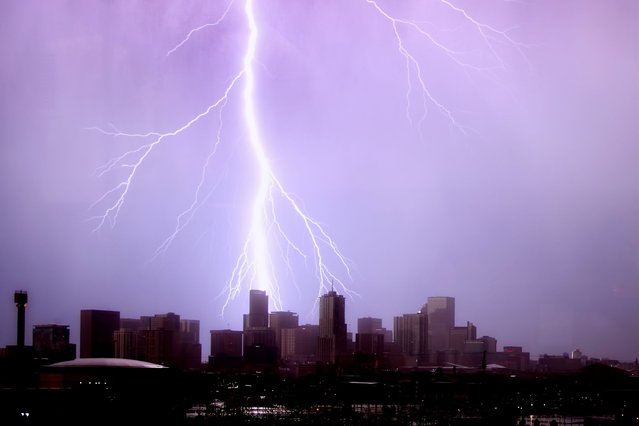 A huge blast of purple-tinged lightning strikes a skyscraper in Denver, Colorado. (Photo by Greg Thow/Barcroft Media)
