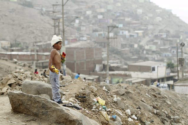 A boy stands with his toys during Christmas celebration in Huaycan on the outskirts of Lima, Peru December 15, 2015. (Photo by Janine Costa/Reuters)