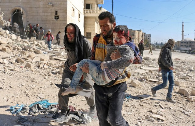 A Syrian civil defence volunteer, known as the White Helmets, carries a boy rescued from the rubble following a reported barrel bomb attack on the Bab al- Nairab neighbourhood of the northern Syrian city of Aleppo on November 24, 2016. (Photo by Ameer Alhalbi/AFP Photo)
