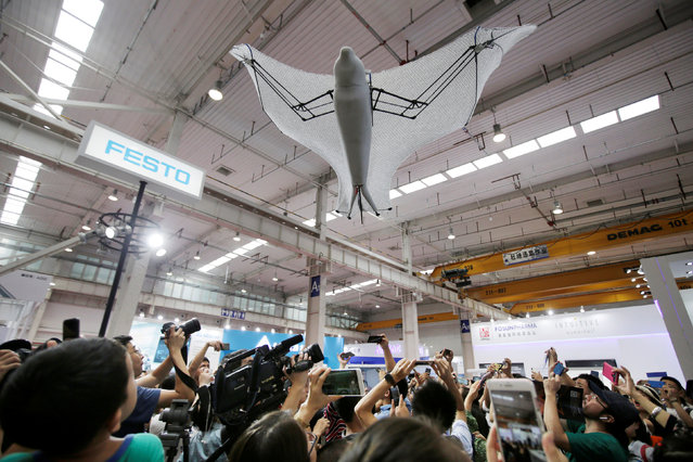 Visitors take pictures of a bionic flying fox at Festo's booth at the WRC in Beijing, China on August 15, 2018. (Photo by Jason Lee/Reuters)