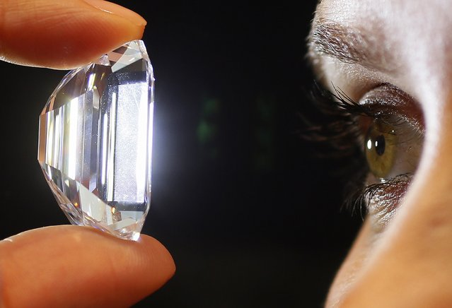 A staff member holds a 100-carat perfect diamond in a classic emerald-cut at Sotheby's auction house in central London, February 13, 2015. The diamond is expected to fetch between $19-25 million at the auction house's Magnificent Jewels auction in New York on April 21. (Photo by Stefan Wermuth/Reuters)