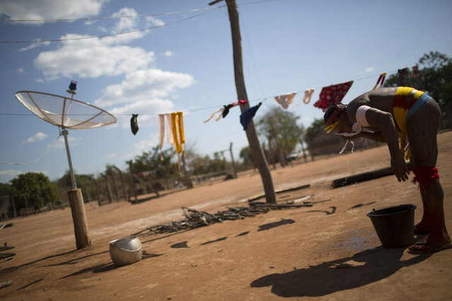 """A Waura Indian man washes his face next to a satellite dish, during this year's """"quarup"""", a ritual held over several days to honour in death a person of great importance to them, in the Xingu National Park, Mato Grosso State, August 24, 2013. This year the Waura tribe honoured their late cacique (chief), Atamai, who died in 2012, for his work creating the Xingu Park and his important contribution in facilitating communication between white Brazilians and Indians. (Photo by Ueslei Marcelino/Reuters)"""