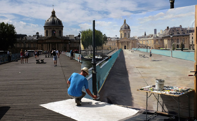 Spanish artist Alberto Martin Giraldo works on a trompe-l'oeil painting at the Pont des Arts in Paris on July 18, 2015. (Photo by Miguel Medina/AFP Photo)