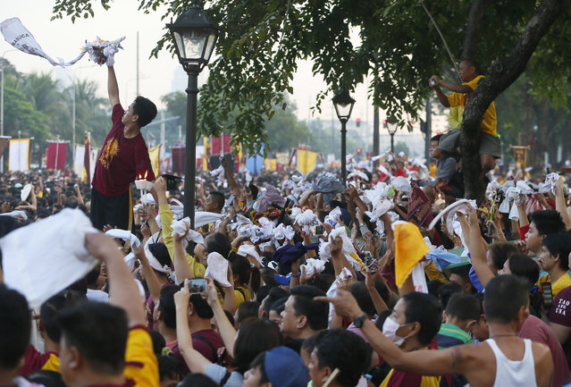 Catholic devotees wave mostly white towels as the image of the Black Nazarene passes by in a raucous procession to celebrate its feast day in Manila, Philippines, Saturday, January 9, 2016. (Photo by Bullit Marquez/AP Photo)