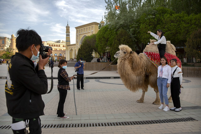 Tourists pose for photos with a camel outside the Id Kah Mosque in Kashgar in western China's Xinjiang Uyghur Autonomous Region, as seen during a government organized trip for foreign journalists, Monday, April 19, 2021. (Photo by Mark Schiefelbein/AP Photo)