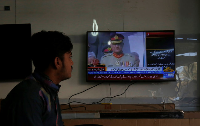 A salesman watches incoming Army Chief of Staff Lieutenant General Qamar Javed Bajwa during the handover ceremony broadcasted on a television while waiting for customers at an electronics shop in Karachi, Pakistan November 29, 2016. (Photo by Akhtar Soomro/Reuters)