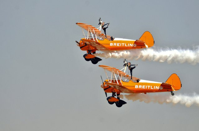 "Members of the Breitling Wingwalkers perform during the inauguration ceremony of the ""Aero India 2015"" air show at Yelahanka air base in the southern Indian city of Bengaluru February 18, 2015. India's prime minister Narendra Modi has asked global defence contractors to transfer more technology to the country as part of the lucrative deals that they win to modernise its armed forces. (Photo by Abhishek N. Chinnappa/Reuters)"