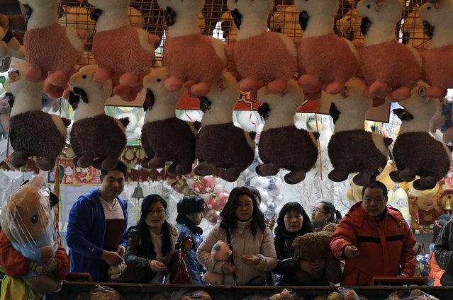 Visitors play games underneath toy sheep  at Chaoyang Park's International Spring Carnival for the Lunar New Year in Beijing Saturday, February 21, 2015. (Photo by Andy Wong/AP Photo)